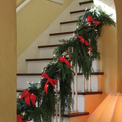 Evergreen garland and red ribbons on a stairway   Favorite Thanksgiving Traditions with Burkholder Landscape