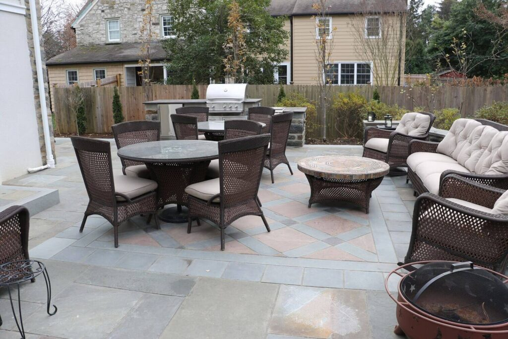 Natural Cleft Full Color Flagstone Patio with carpet detail of Tan Flagstone Squares and Plum Flagstone details | Flagstone Patio | Burkholder Brothers