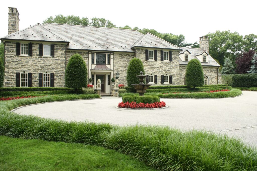 Front view of Large brick estate with circle drive and ornamental grassesEstate Landscape Management - Burkholder Landscape