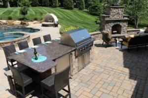 patio kitchen with fireplace pool and hot tub - Burkholder
