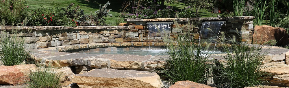 Looking for Landscaping Design Near me - Contact Burkholder Landscaping - Retaining wall surrounding pool with waterfall and surrounded by softscape plants and trees and rocks