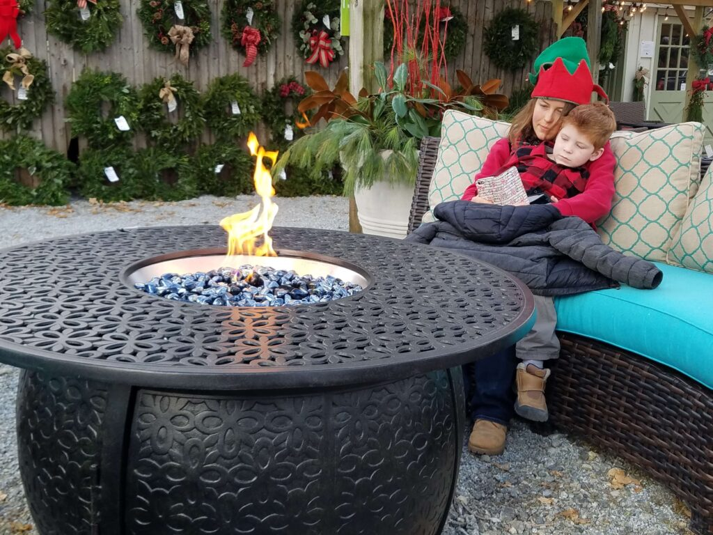 Woman and child sitting by a firepit | 2020 Holiday Market | Burkholder Brothers