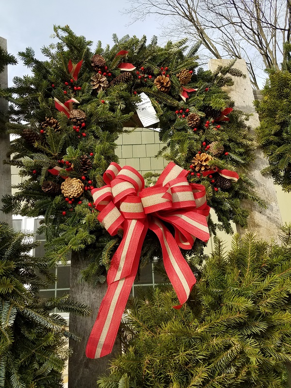 Wreath with pine cones berries and red with canvas ribbon at the Burkholder Holiday Pop Up Market