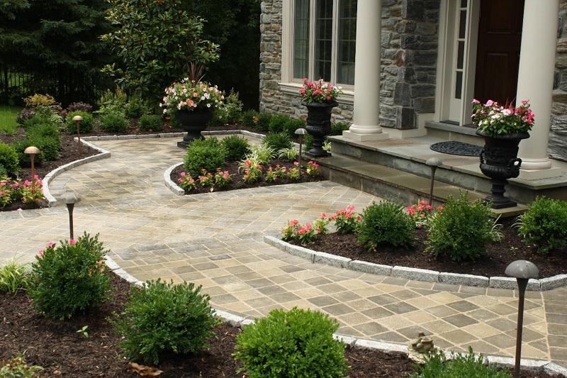 Front stone walk with manicured plant beds and columned entrance | Advantages of Techo-Bloc | Burkholder Brothers Landscape