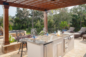 Pergola over outdoor kitchen with chaise lounges and a spa in the background
