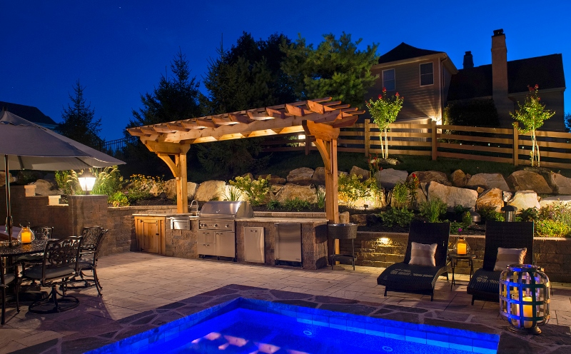 Photo of backyard pool and kitchen during night   Benefits of outdoor lighting   Burkholder Brothers