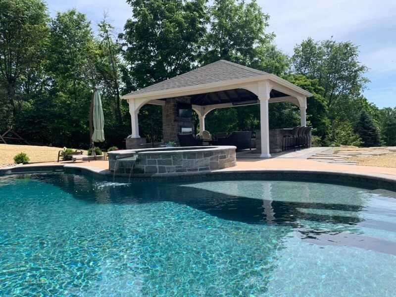 Photo of a pool in backyard with pavilion and fireplace | New Landscaping Projects | Burkholder Brothers