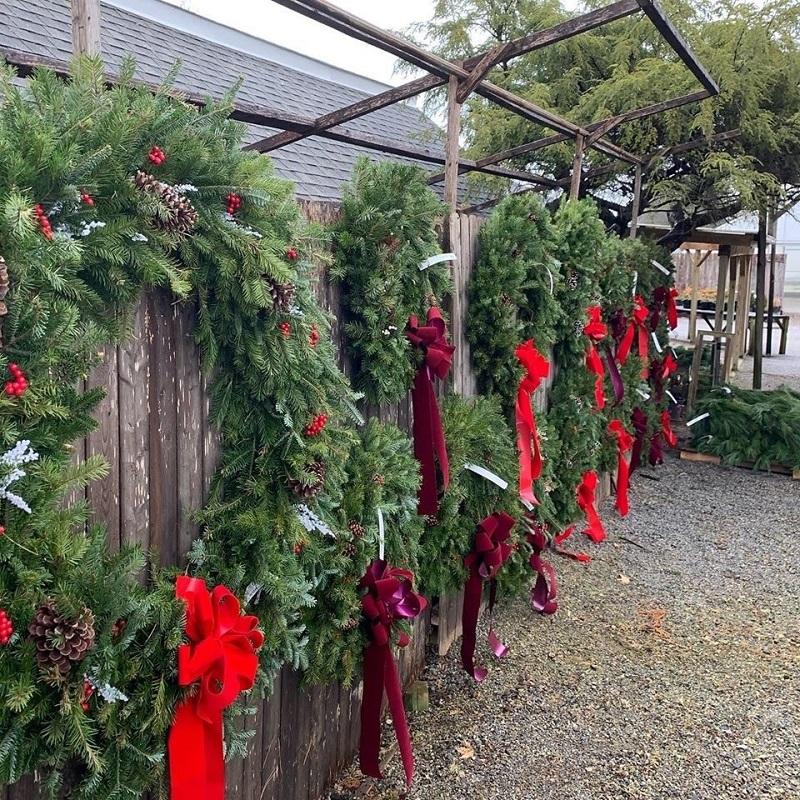 Wreaths hanging on fence at market | 2020 Holiday Market | Burkholder Brothers